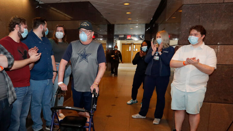 COVID-19 patient Stephen Donelson is applauded by family and health care professionals