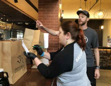 Moriah Guise and Dustin Mitchell check takeout orders at Iron Hill Brewery. (Cris Barrish/WHYY)