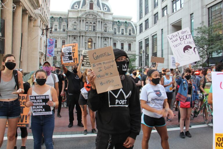 Protesters march south on Broad Street after a rally at City Hall demanding justice for Jacob Blake, a Black man who was shot by police in Kenosha, Wisconsin. (Emma Lee/WHYY)