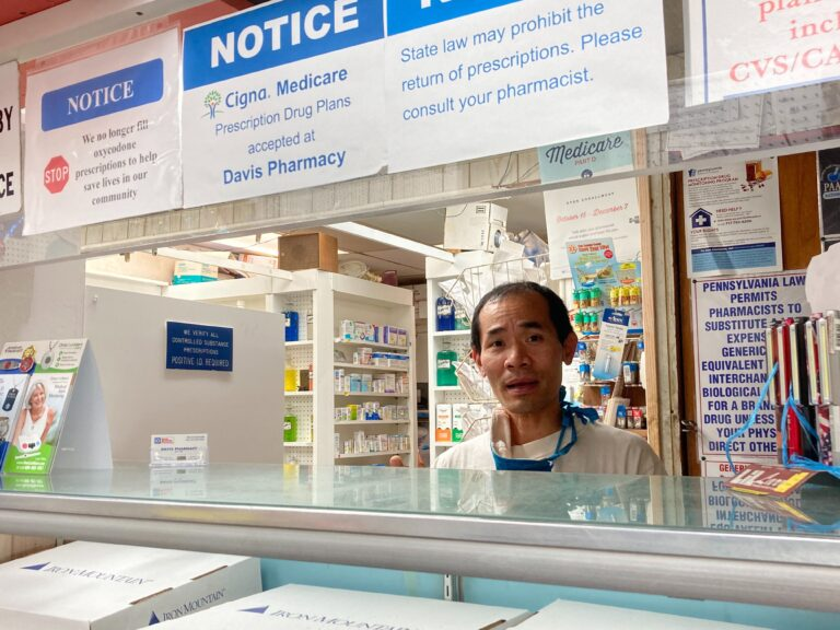 Pharmacist Steven Nguyen works at Davis Pharmacy on Baltimore Ave. He's been calling the US Postal Service's line for days trying to track down customer packages (Hannah Chinn/WHYY)