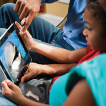 A child watching PBS Kids programing on a tablet at home
