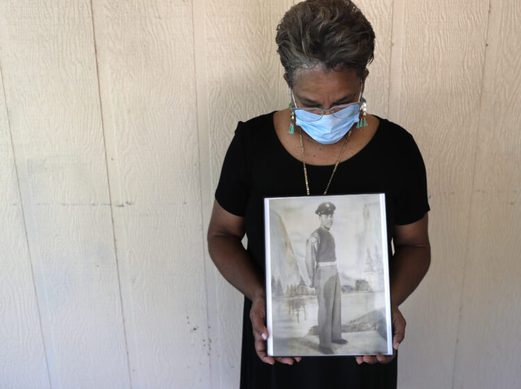 Belvin Jefferson White poses with a portrait of her father Saymon Jefferson, who died from COVID-19, in Baton Rouge, La., in May. (Gerald Herbert/AP)