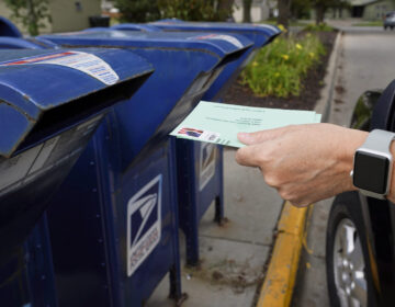 A person drops applications for mail-in-ballots into a mail box