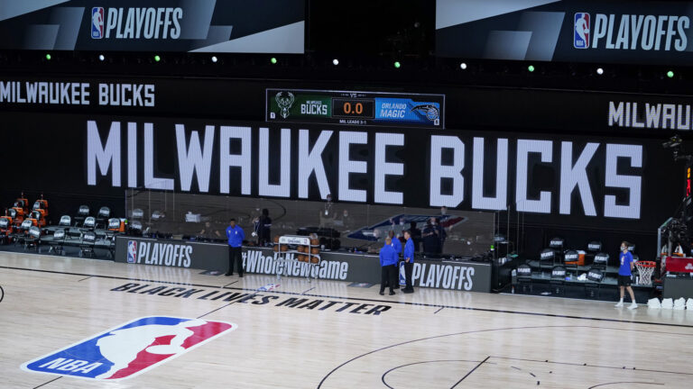 Officials stand beside an empty court at the scheduled start of an NBA basketball playoff game between the Milwaukee Bucks and the Orlando Magic, Wednesday in Lake Buena Vista, Fla. The Bucks didn't take the floor in protest against racial injustice and the shooting of Jacob Blake, a Black man, by police in Kenosha, Wisconsin.