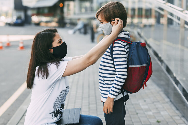 A mother wearing a face mask adjusting a face mask on her son before he goes to school