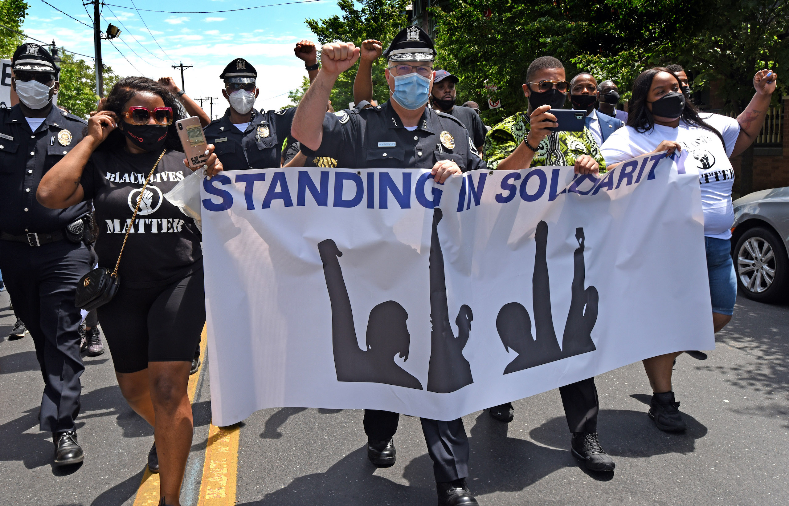 Camden County Police Chief Joe Wysocki raises a fist while marching with Camden residents