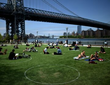 A new study has found that parks in low-income and majority nonwhite communities are smaller and serve a larger number of people per park acre. People are seen here relaxing in May in Brooklyn's Domino Park. (Johannes Eisele/AFP via Getty Images)