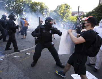 A law enforcement officer raises a baton and tear gas is fired during protests near the White House on June 1. (Jose Luis Magana/AFP via Getty Images)