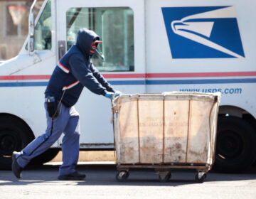 Postal workers prepare mail for delivery