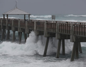 Waves crash along the Juno Beach Pier as Tropical Storm Isaias passes through the area Sunday in Juno Beach, Fla. The storm is now headed toward the Carolinas.