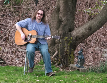 Musician Jay Mage singing and playing guitar outside