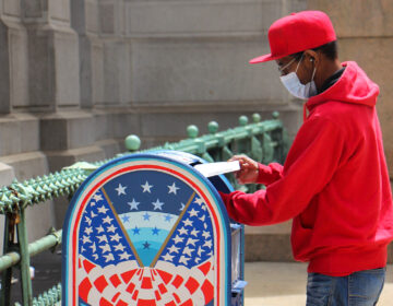 A voter places his mail-in ballot in a box outside City Hall.