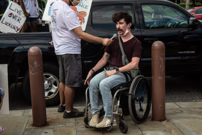 Liam, an organizer from Adapt, demanded equal healthcare for people with disabilities
