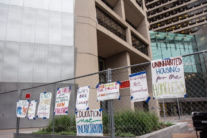 Protesters taped signs to the fence surrounding the office building of Joe Biden's campaign headquarters
