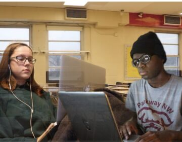 two teenaged students looking at a laptop