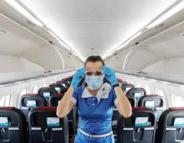 A flight attendant adjusts protective glasses. There has been little documentation about COVID-19 transmission on planes.
