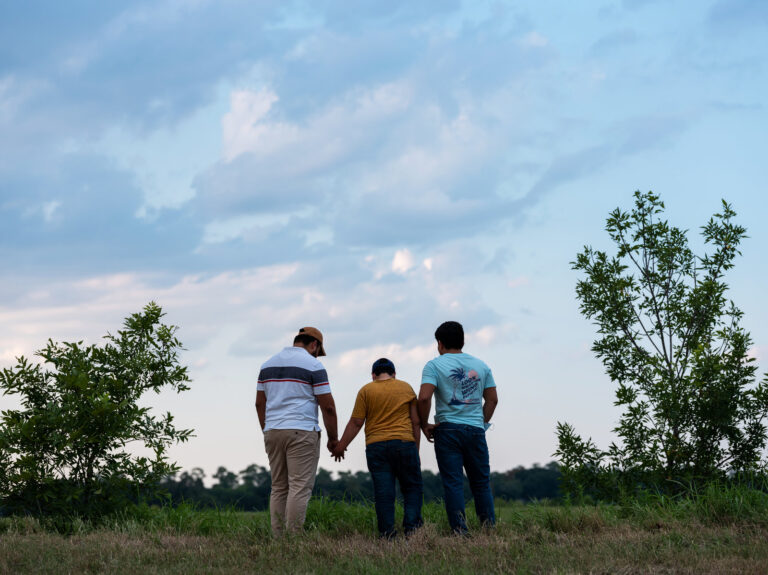 Honduran migrants, Ricardo Sr., (left), his son Ricardo Jr., 13, and his cousin Jorge, 16, walk near their home in Texas. When the two teenage boys crossed the border illegally into Texas last month, they turned themselves into Border Patrol. They were later escorted to a hotel by armed men in civilian clothes. (Scott Dalton for NPR)