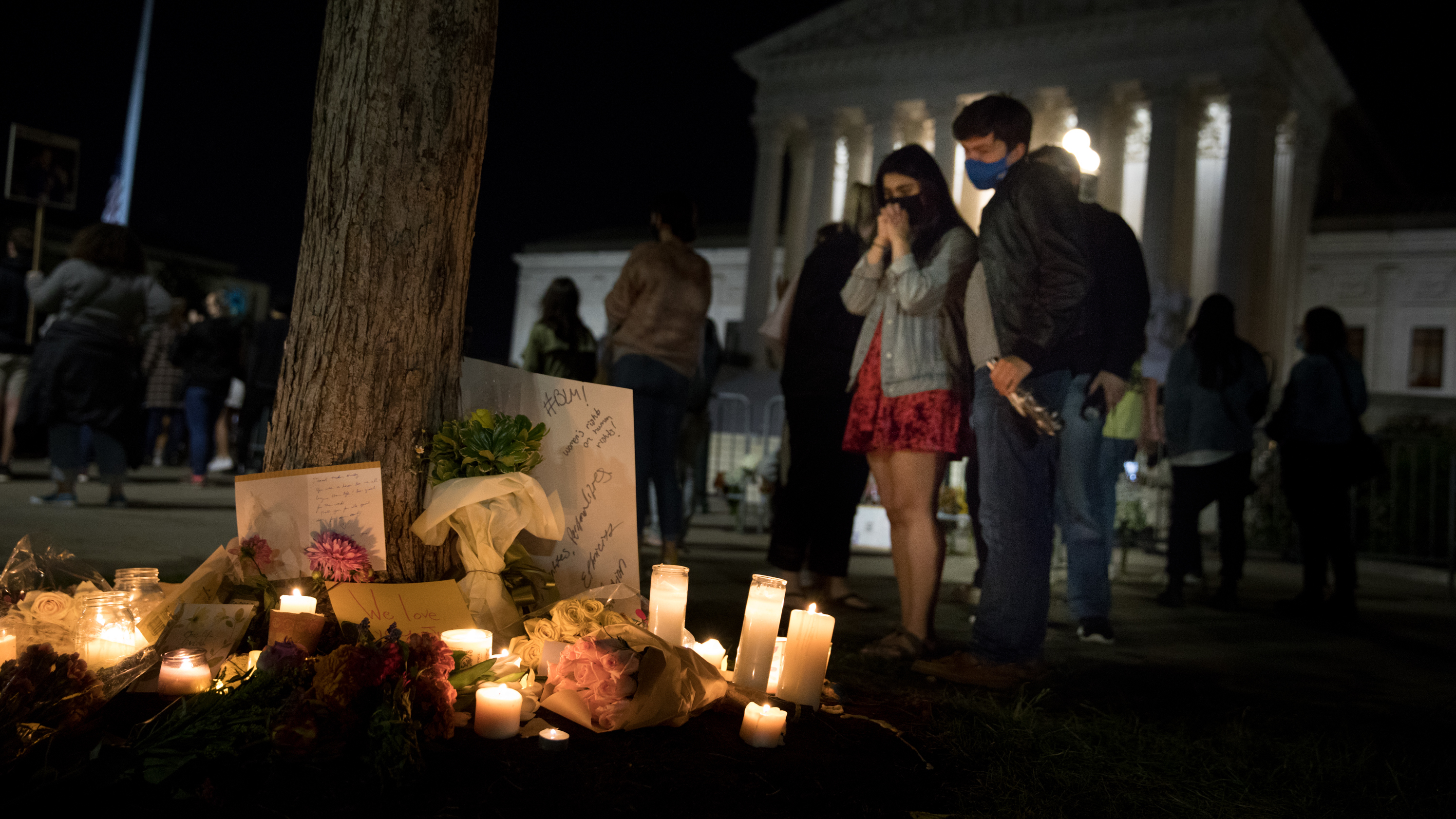 Makek Ahmad (left) and Jack Korologos(right) stop to look at the candles, signs and flowers left in front of the U.S. Supreme Court.