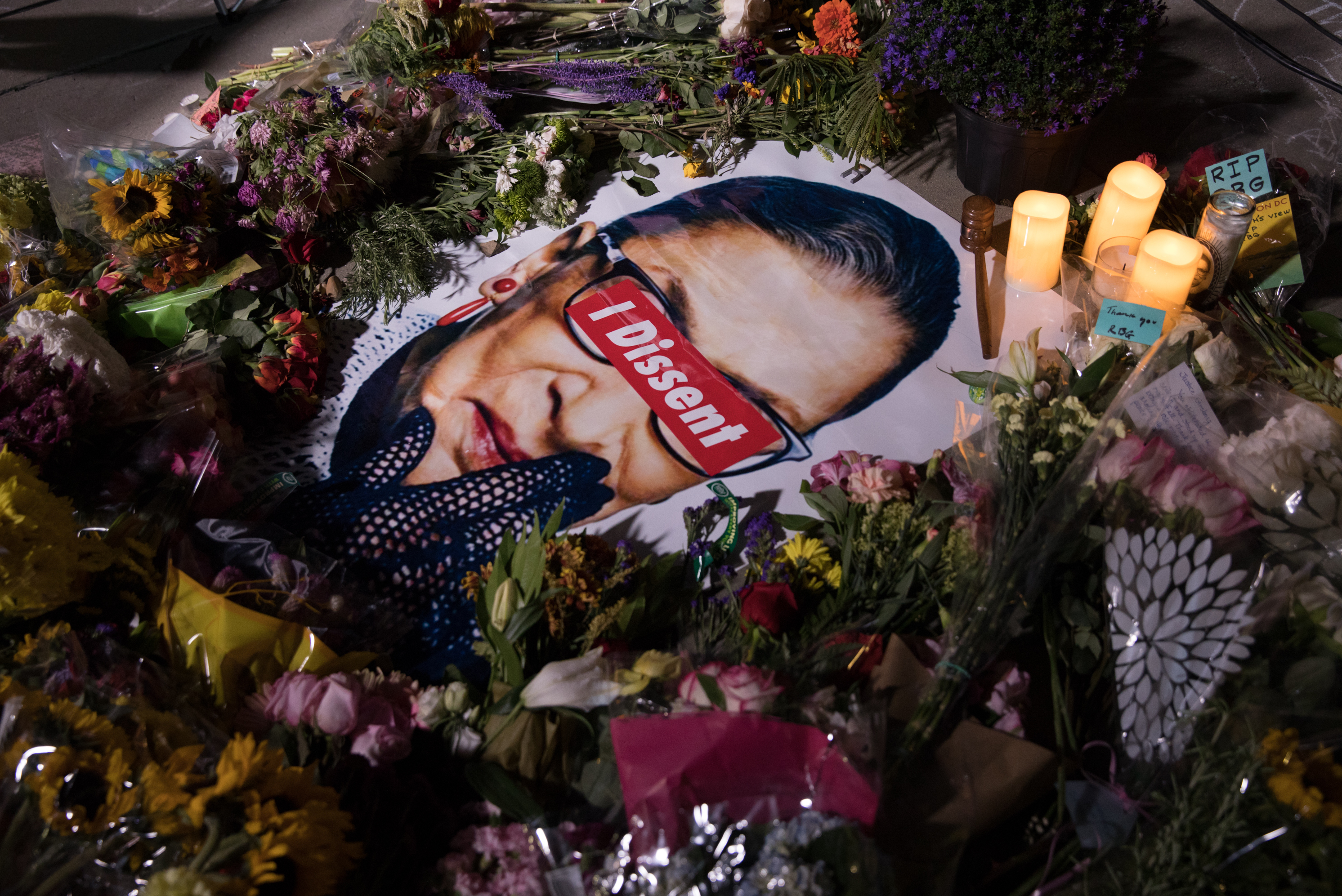 An image of Ruth Bader Ginsburg sits surrounded by flowers during the vigil.