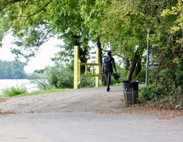 A fisherman walks along the Schuylkill River Trail at Bartram's Gardens. (Emma Lee/WHYY)