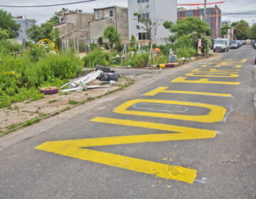 """At the César Andreu Iglesias CommunityGarden in Kensington, the words """"Not for sale"""" are painted on the street as a message to developers and the city. (Kimberly Paynter/WHYY)"""