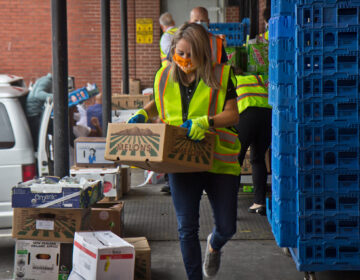 Jane Clements-Smith, executive director of Feeding PA, helps load trucks at Philabundance's South Philly location. (Kimberly Paynter/WHYY)
