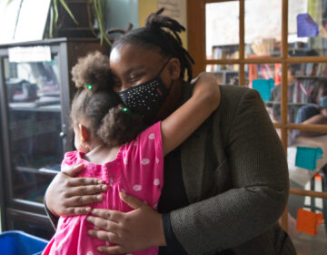 Tree House Books program director Sabriaya Shipley hugs Ayah Robinson, 8. (Kimberly Paynter/WHYY)
