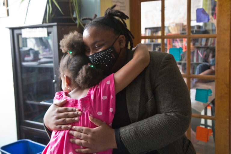 Tree House Books program director Sabriaya Shipley hugs Ayah Robinson, 8. (Kimberly Paynter/WHYY)