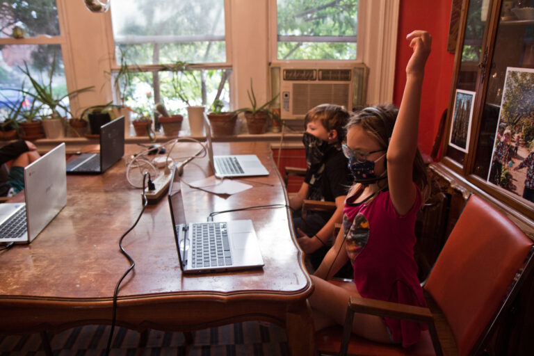 Two kids at kitchen table, wearing masks during virtual learning