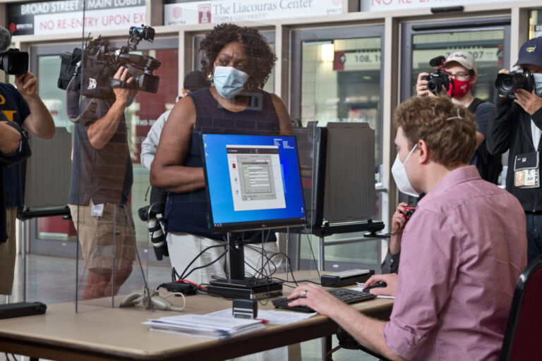 The first voter at the Liacouras Center satellite election office, Priscilla Bennett, first requests a ballot, which will be printed at the office. (Kimberly Paynter/WHYY)
