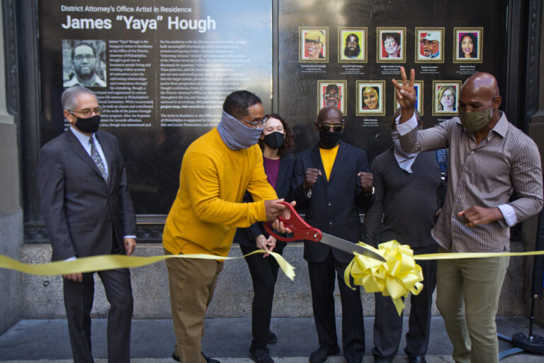"James ""Yaya"" Hough, first-ever artist-in-residence at the Philadelphia District Attorney's Office, cuts a ribbon with DA Larry Krasner (left), Mural Arts' Jane Golden, (third from left), Michael ""Smokey"" Wilson, (third from right) and boxing champion Bernard Hopkins (right). (Kimberly Paynter/WHYY)"
