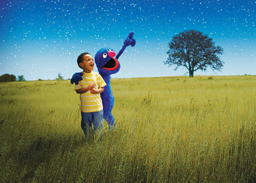 A child with Elmo under a starry night sky