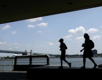 People are silhouetted as they walk on Penn's Landing in view of the Benjamin Franklin Bridge in Philadelphia. (Matt Rourke/AP Photo)
