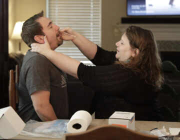 Mendy McNulty swabs the nose of her husband, Joe, in their home on Tuesday, July 28, 2020.  (AP Photo/Mark Humphrey)