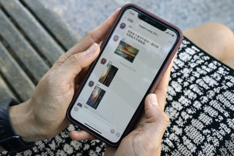 Sha Zhu, of Washington, shows the app WeChat on her phone, which she uses to keep in touch with family and friends in the U.S. and China, Tuesday Aug. 18, 2020, in Washington. (AP Photo/Jacquelyn Martin)