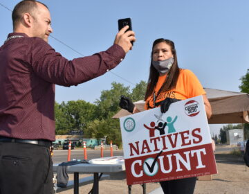 Activist Lauri Dawn Kindness, right, speaks at the Crow Indian Reservation, in Lodge Grass, Mont. on Wednesday, Aug. 26, 2020, as Lodge Grass Mayor Quincy Dabney records her for a social media campaign to increase Native American participation in the U.S. census. (AP Photo/Matthew Brown)