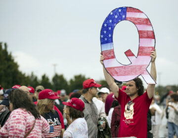 David Reinert holding a Q sign waits in line with others to enter a campaign rally with President Donald Trump Republican U.S. Senate candidate Rep. Lou Barletta, R-Pa., Thursday, August 2, 2018 in Wilkes-Barre, Pa. (AP Photo/Matt Rourke)