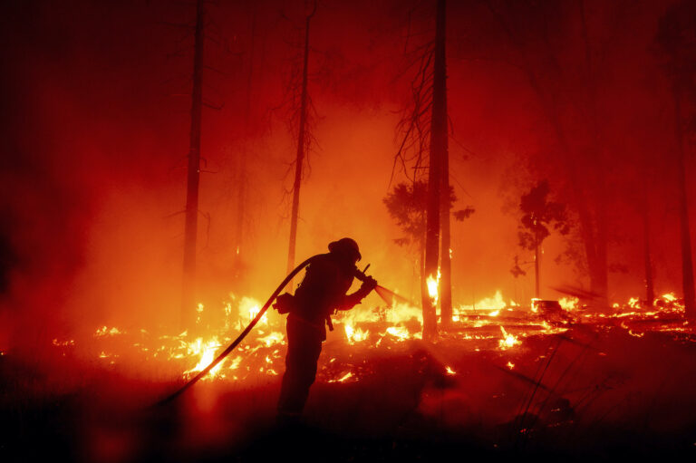 FILE - In this Sept. 7, 2020, file photo, a firefighter battles the Creek Fire as it threatens homes in the Cascadel Woods neighborhood of Madera County, Calif. (AP Photo/Noah Berger,File)