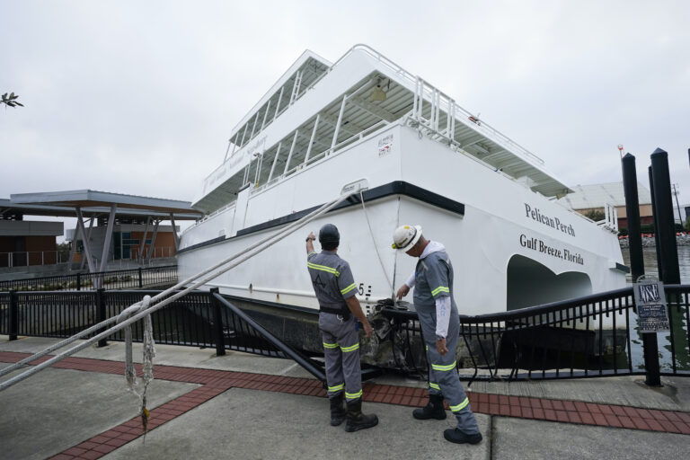 Workers look over a damaged ferry, Thursday, Sept. 17, 2020, in Pensacola, Fla. (AP Photo/Gerald Herbert)