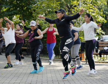 Yeni Salazar, center, leads a Zumba class in Queen's Elmhurst Memorial Park, Monday, Sept. 21, 2020 in New York. Salazar has been leading the morning outdoor classes since May because the COVID-19 pandemic has closed her health club. (AP Photo/Mark Lennihan)