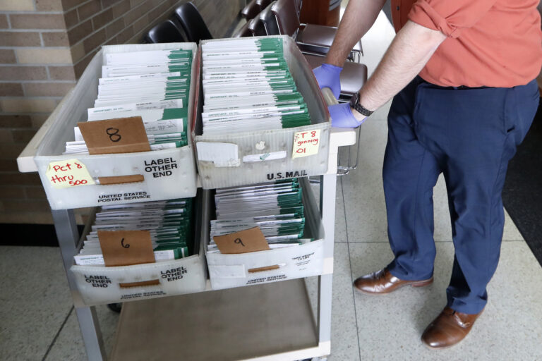 In this May 5, 2020, file photo, absentee ballots to be counted are moved at City Hall in Garden City, Mich. (AP Photo/Paul Sancya, File)