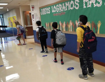 Students physically distance as they walk to their classroom