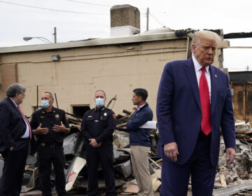 President Donald Trump turns around after talking with law enforcement officials Tuesday, Sept. 1, 2020, as he tours an area damaged during demonstrations after a police officer shot Jacob Blake in Kenosha, Wis. At left, Attorney General William Barr and acting Homeland Security Secretary Chad Wolf talk with police officers. (AP Photo/Evan Vucci)