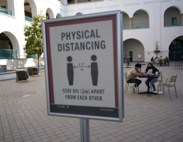 People sit at tables at San Diego State University Wednesday, Sept. 2, 2020, in San Diego. San Diego State University on Wednesday halted in-person classes for a month after dozens of students were infected with the coronavirus. (AP Photo/Gregory Bull)