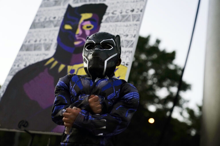 Mason Wilkes, 4, of South Carolina, poses for his father in a Black Panther costume, in front of a paining during a Chadwick Boseman Tribute on Thursday, Sept. 3, 2020, in Anderson, S.C. (AP Photo/Brynn Anderson)