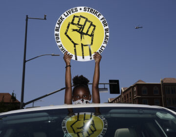 In this July 20, 2020, file photo, Audrey Reed, 8, holds up a sing through the sunroof of a car during a rally in Los Angeles. Ahead of Labor Day, major U.S. labor unions say they are considering work stoppages in support of the Black Lives Matter movement. (AP Photo/Jae C. Hong)
