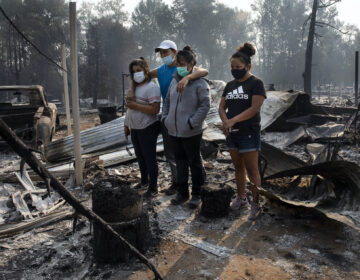 The Reyes family looks at the destruction of their trailer at the Coleman Creek Estates where 121 trailers burned as wild fires devastate the region on Thursday in Portland, Ore. The Reyes family lived in the park for 20 years. (AP Photo/Paula Bronstein)