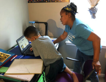 Tiffany Shelton helps her 7-year-old son, P.J. Shelton, a second-grader, during an online class at their home in Norristown, Pa., on Thursday, Sept. 3, 2020. (AP Photo/Michael Rubinkam)