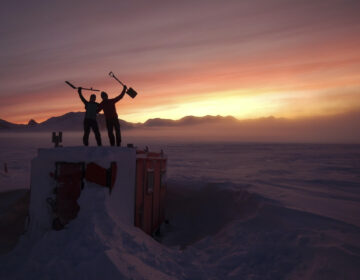 In this handout photo provided by British Antarctic Survey, field guides Sarah Crowsley, left, and Sam Hunt, right, pose for a photo after digging out the caboose, a container used for accommodation that can be moved by a tractor, at Adelaide island, in Antarctica on Friday, June 19, 2020. (Robert Taylor/British Antarctic Survey via AP)