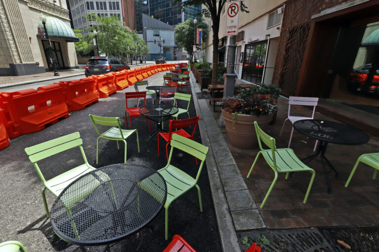 Orange barriers enclose chairs and tables that will be used for dining along Sixth Street between Liberty and Penn avenues
